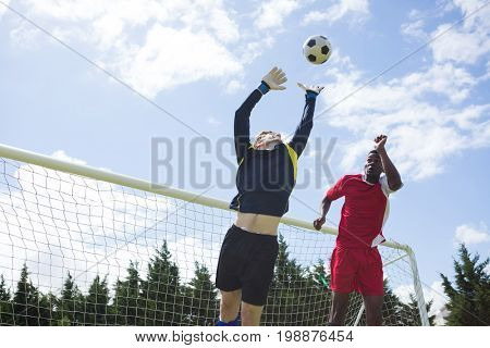 Male soccer players playing against sky during sunny day