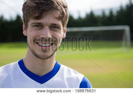 Portrait of smiling male soccer player with arms crossed standing on playing field