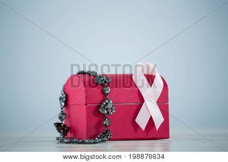 Close-up of jewelry with red box and pink Breast Cancer Awareness ribbon against gray background