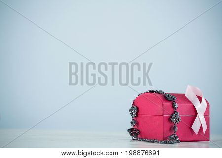 Pink Breast Cancer Awareness ribbon and jewelry on red box against gray background