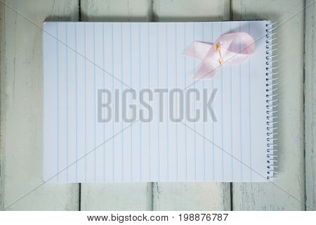 Overhead view of pink Breast Cancer Awareness ribbon and spiral notepad on wooden table