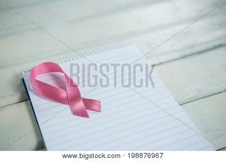 High angle view of pink Breast Cancer Awareness ribbon and spiral notepad on wooden table