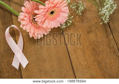 High angle view of pink Breast Cancer Awareness ribbon by gerbera flowers on wooden table