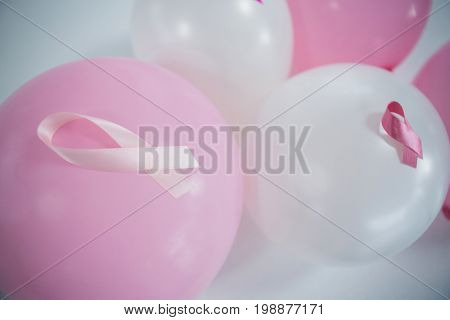 High angle view of pink Breast Cancer Awareness ribbons on balloons against white background