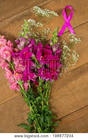 Overhead view of pink Breast Cancer Awareness ribbon by flowers on wooden table