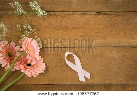 Directly above view of pink Breast Cancer Awareness ribbon by gerbera flowers on wooden table