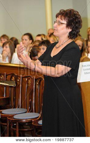 KAPOSVAR, HUNGARY - AUGUST 26: Judit Majnay conducts at the IV. Pannonia Cantat Youth Choir Festival August 26, 2010 in Kaposvar, Hungary