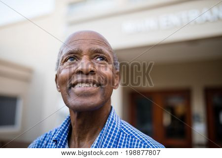 Close-up of thoughtful senior man smiling while looking up at nursing home