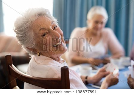 Smiling senior woman playing cards with friends at table in nursing home