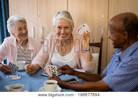 Happy senior people playing cards while having coffee at nursing home