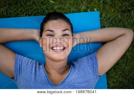 High angle portrait of smiling trainer lying on exercise mat at park