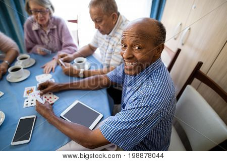Happy senior man playing cards with friends while having coffee at table in nursing home