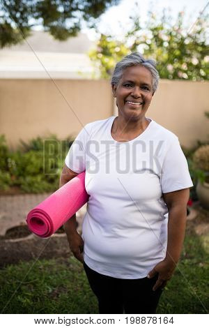 Smiling senior woman carrying exercise mat while standing at park