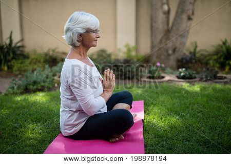 Side view of senior woman meditating in prayer position at park