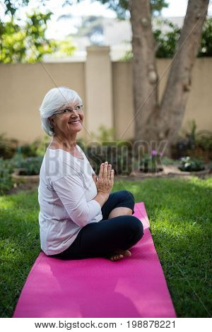 Side view of smiling senior woman meditating in prayer position at park