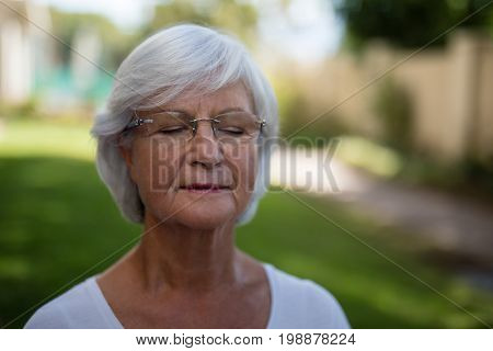 Close-up of senior woman with closed eyes at park