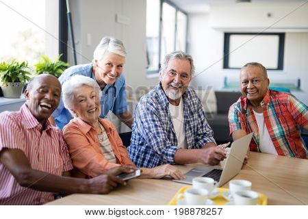 Portrait of smiling practitioner with senior people by table at nursing home