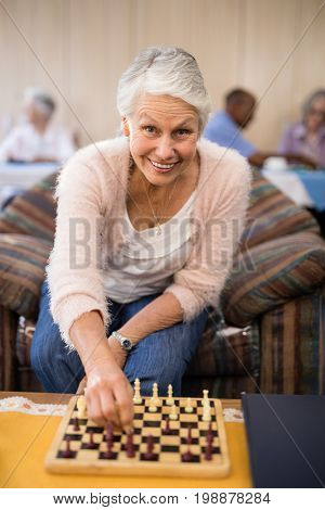 Portrait of confident senior woman playing chess at table while sitting on couch in nursing home