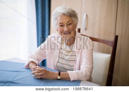 Portrait of smiling senior woman sitting with hands clasped at table in nursing home