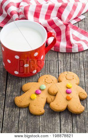 Two gingerbread men and mug of milk. Xmas gingerbread. Laughing gingerbread man.