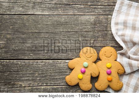 Two sweet gingerbread men on old wooden table. Top view. Xmas gingerbread. Laughing gingerbread man.