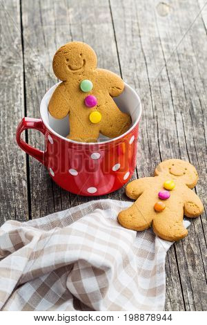 Gingerbread man in mug on old wooden table. Xmas gingerbread. Laughing gingerbread man.