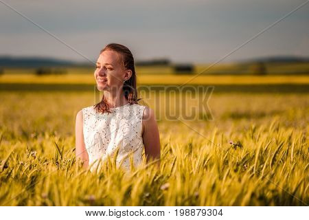 Beautiful woman in white dress on golden yellow wheat field in warm sunshine under dramatic sky, fresh vibrant colors, at Rhine Valley (Rhine Gorge) in Germany
