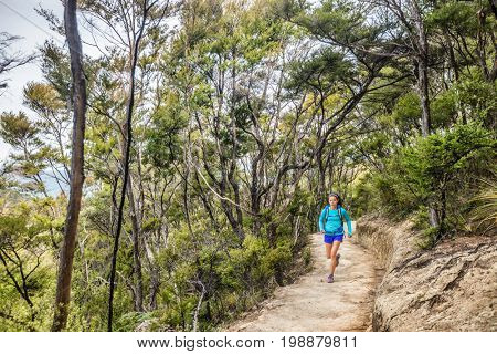Trail runner woman running in forest nature path outdoors. Sport athlete girl training outdoor on adventure travel. Ultra run marathon workout.