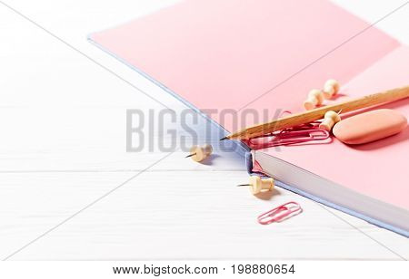 An open notebook, pencil and paperclips on a white background