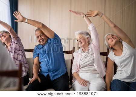 Senior people stretching while sitting on chairs at retirement home