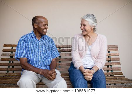 Smiling senior man and woman looking at each other while sitting on bench against wall at retirement home