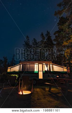 Campsite at night with glow from RV trailer and campfire tall pine trees and night stars. Outdoors camping and adventure concepts background with space for text. Vertical composition