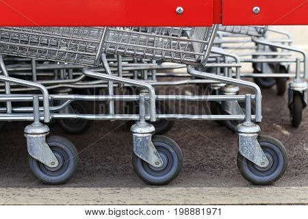 Wheels of shopping trolleys close-up. Shiny trolleys closeup. Details of shopping cart.
