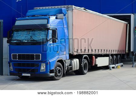 Truck at loading docks close-up. Cargo transportation theme.