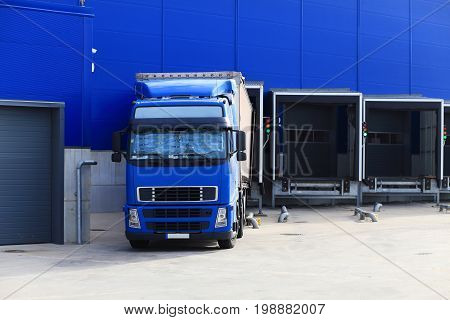 Blue truck at loading docks. Truck unloading cargo. Cargo transportation background.