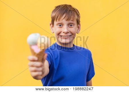 Blonde beautiful boy with freckles and blue T-shirt holding ice cream. studio shot on yellow background.