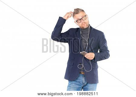 Middle adult man in eyeglasses listening to music on smartphone through earphones