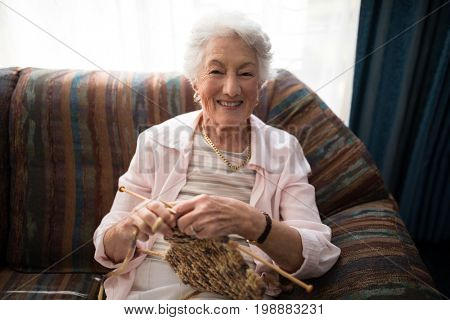 Portrait of smiling senior woman knitting while sitting on sofa against window at retirement home