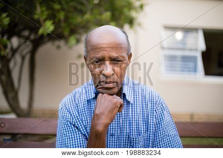 Depressed senior man sitting with hand on chin against retirement home