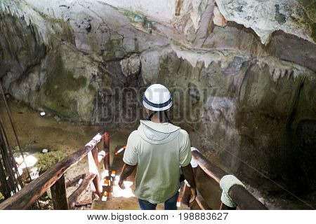 Person wearing helmet descending into a cave going down stairs. Natural patches of sun aerial roots descending into the hole colorful walls with stalactites can be seen in the background.