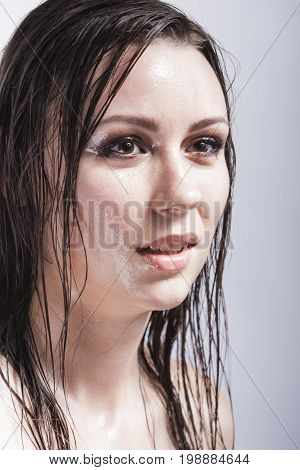 Beauty Concepts and Ideas. Portrait of Caucasian Sensual Brunette Girl Showing Wet and Shining Skin and Wet Hair. Creative Makeup. against Grey. Vertical Image Composition