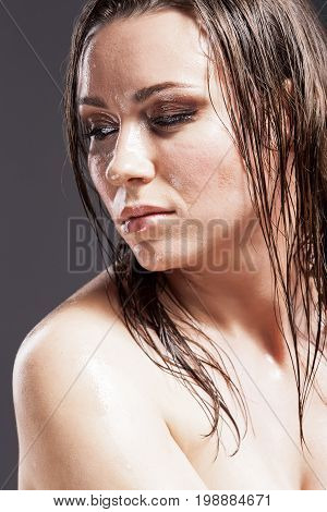 Beauty Concepts. Portrait of Sensual Tanned Caucasian Brunette Woman With Sad Expression with Wet and Shining Skin and Wet Hair. Against Dark Grey Background. Vertical Image Composition
