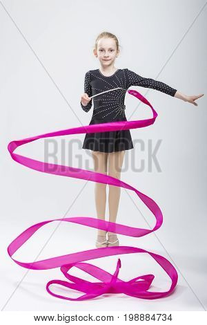 Portrait of Caucasian Female Rhythmic Gymnast In Professional Competitive Black Sparkling Starry Suit Doing Artistic Ribbon Spirals Exercises in Studio. Vertical Image