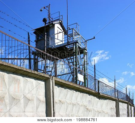 A prison tower with a concrete fence and barbed wire, the protection of convicts