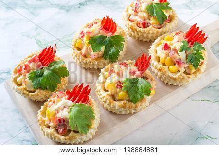 Vol-au-vent filled with chicken salad sweet pepper egg and corn. Festive appetizer for Christmas Valentine's Day Easter. Colorful snack of French cuisine from air puff pastry with filling