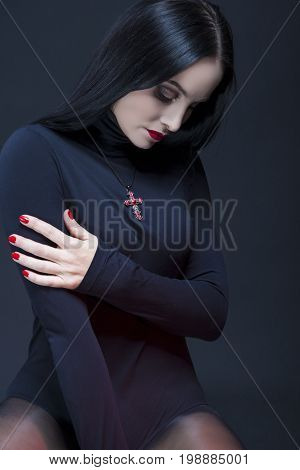 Beauty Concepts. Studio Portrait of Mid Aged Sexy Relaxed Caucasian Brunette Woman Posing in Black Body Suit with Symbolyc Cross Necklace. Vertical Orientation