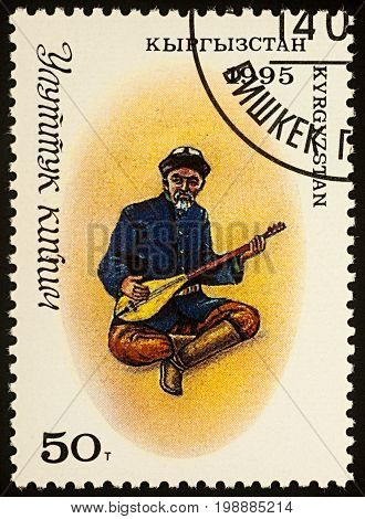Moscow Russia - August 07 2017: A stamp printed in Kyrgyzstan shows man in traditional Kyrgyz costume with a stringed musical instrument (comus) series