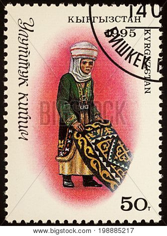 Moscow Russia - August 07 2017: A stamp printed in Kyrgyzstan shows woman in traditional Kyrgyz costume with carpet series