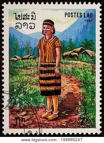 Moscow Russia - August 06 2017: A stamp printed in Laos shows woman in a national Lao clothes against the backdrop of a mountain village series