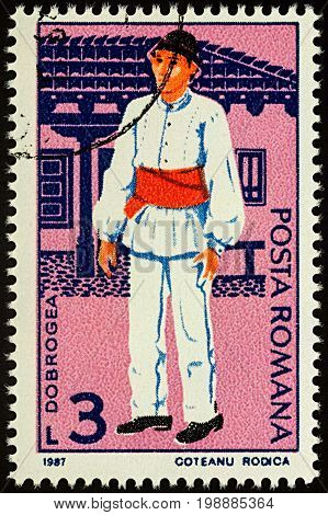 Moscow Russia - August 07 2017: A stamp printed in Romania shows young man in Romanian national costume Dobrogea region series